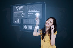 Businesswoman with cellphone and virtual screen. Pretty young businesswoman talking on the cellphone while touching financial statistics on the futuristic screen Royalty Free Stock Photography