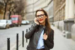 Businesswoman on cellphone walking down the street while talking Stock Photo