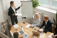 Businesswoman leader giving presentation explaining team goals a. Businesswoman ceo boss in suit presenting corporate strategy pointing on flip chart at group stock photography