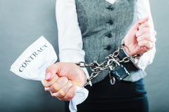 Businesswoman with chained hands holding contract Stock Photography
