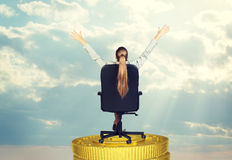 Businesswoman in chair on coins stack, rear view Stock Image