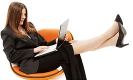 Businesswoman in chair with laptop Stock Photos