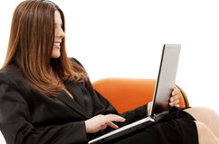 Businesswoman in chair with laptop Stock Images