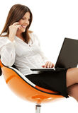 Businesswoman in chair with laptop and phone Royalty Free Stock Photos
