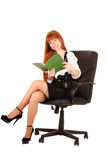 Businesswoman  in chair reading Stock Photography