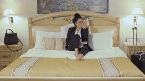Businesswoman changes the channels on tv with remote control. Young businesswoman in black suit sits on the bed in a hotel room and relax after a long work day stock footage