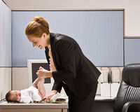 Businesswoman changing baby diaper at desk Stock Image