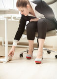 Businesswoman changing shoes under table at office Royalty Free Stock Photos