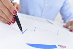Businesswoman with a chart with an upward trend. Closeup of a businesswoman at her office desk full of graphs and charts, observes a chart with an upward trend Royalty Free Stock Photo