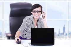 Businesswoman chatting at office using phone and laptop Stock Image