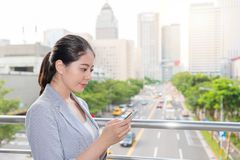 Businesswoman checking the air quality index. Beautiful businesswoman checking the air quality index on the smartphone app online on the rush hour traffic time stock photo