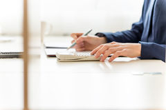 Businesswoman checking and analysing a report. View of the arms of a businesswoman sitting working at her desk in the office checking and analysing a report with Royalty Free Stock Photos