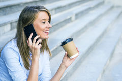 A businesswoman checking email via mobile phone and holding a coffee cup against urban scene Stock Images