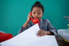 Businesswoman checking file while talking on land line. At desk against blue background Stock Photos