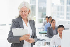 Businesswoman checking her clipboard while team work using computer Stock Photos