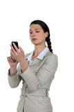 Businesswoman checking her Smartphone. A businesswoman checking her Smartphone Stock Image