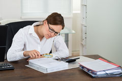 Businesswoman Checking Invoice With Magnifying Glass Royalty Free Stock Photos