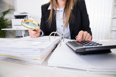 Businesswoman Checking Invoice With Magnifying Glass Royalty Free Stock Images