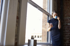 Businesswoman Checking Phone Standing By Office Window Stock Photo