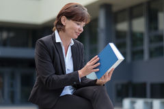 Businesswoman checking the spine of a book. Businesswoman checking the spine and title of a large hardcover book as she sits outdoors outside the office building Royalty Free Stock Photos