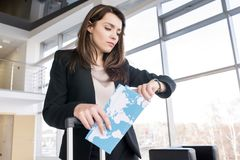 Businesswoman Checking Time in Airport. Waist up portrait of beautiful businesswoman checking time and holding airplane tickets while waiting for flight in Stock Photo