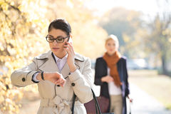 Businesswoman checking time while colleague standing in background at park Stock Photo