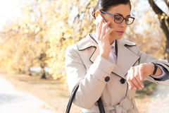 Businesswoman checking time while using cell phone at park Stock Photo