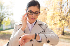 Businesswoman checking time while using smart phone at park Royalty Free Stock Image