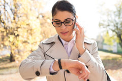 Businesswoman checking time while using smart phone at park Stock Photo