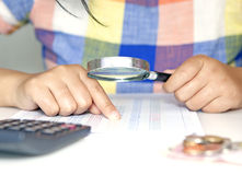 Businesswoman checks the bill with magnifier Royalty Free Stock Photo