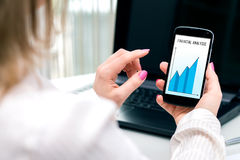 Businesswoman checks the financial analysis on smartphone. Stock Photo