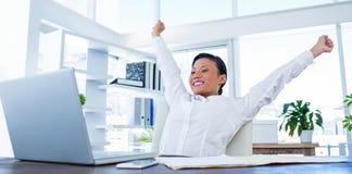 Businesswoman cheering behind laptop computer Stock Photo