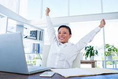 Businesswoman cheering behind laptop computer Royalty Free Stock Images