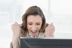 Businesswoman cheering with clenched fists at office desk. Elegant businesswoman cheering with clenched fists at office desk Stock Photo