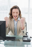 Businesswoman cheering with clenched fists in office. Elegant businesswoman cheering with clenched fists and eyes closed in office Royalty Free Stock Photography