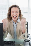 Businesswoman cheering with clenched fists in office. Portrait of an elegant businesswoman cheering with clenched fists in office Stock Photos