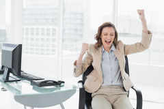 Businesswoman cheering with hands raised in office Stock Photos