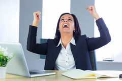 Businesswoman cheering at her desk Royalty Free Stock Photography
