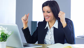 Businesswoman cheering at her desk Royalty Free Stock Photo