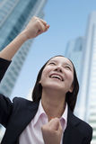 Businesswoman Cheering, Skyscraper in Background Royalty Free Stock Image