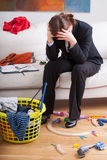 Businesswoman and children's mess. Unhappy businesswoman sitting in the middle of a mess her children made Royalty Free Stock Photography