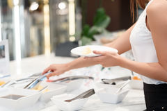 Businesswoman chooses a meal at business buffet Stock Image