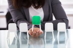 Free Businesswoman Choosing Green Chair Among White Chairs In A Row Royalty Free Stock Photos - 126284118