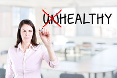 Businesswoman choosing Healthy instead of Unhealthy. Office background. Royalty Free Stock Photo