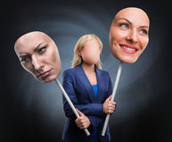 Businesswoman choosing humor. Businesswoman choosing face over grey background Stock Images