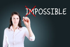 Businesswoman choosing Possible instead of Impossible. Blue background. Royalty Free Stock Photos