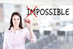 Businesswoman choosing Possible instead of Impossible. Office background. Royalty Free Stock Photo
