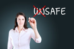 Businesswoman choosing Safe instead of Unsafe. Blue background. Royalty Free Stock Images