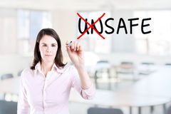 Businesswoman choosing Safe instead of Unsafe. Office background. Businesswoman choosing Safe instead of Unsafe. Office background Royalty Free Stock Photography