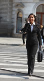 Businesswoman in the city. Young businesswoman on the phone crossing the street in a city Stock Photography